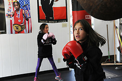 At right, Destiny Garcia, 9, and her twin Cassandra work out on the heavy bags at the Salinas Boxing Club in Closter Park.