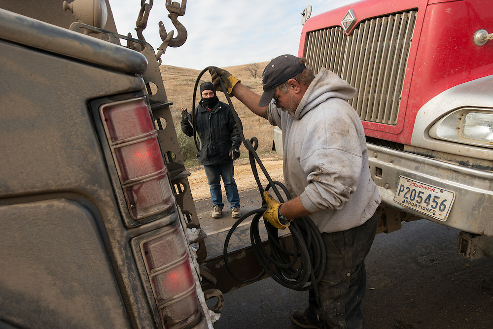 Roberto Arnoldo works at getting his rig towed back onto the road after loosing control of his truck on his first snow driving experience in 11 years just outside of Williston, N.D., Oct 29, 2013.  Arnoldo lost control at 3:30am the previous morning and slept in his truck waiting for the tow truck. The only damage was a blown tire while being pulled out.  Photo Ken Cedeno