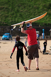 © Licensed to London News Pictures. 06/05/13 A father and son head back from the shore as people start to head to the beach in Tynemouth North East England to enjoy the bank holiday weather as a warm front sits over the country Photo credit : John Millard/LNP
