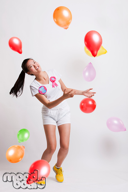 Portrait of playful young woman with multicolored balloons celebrating her birthday against white background
