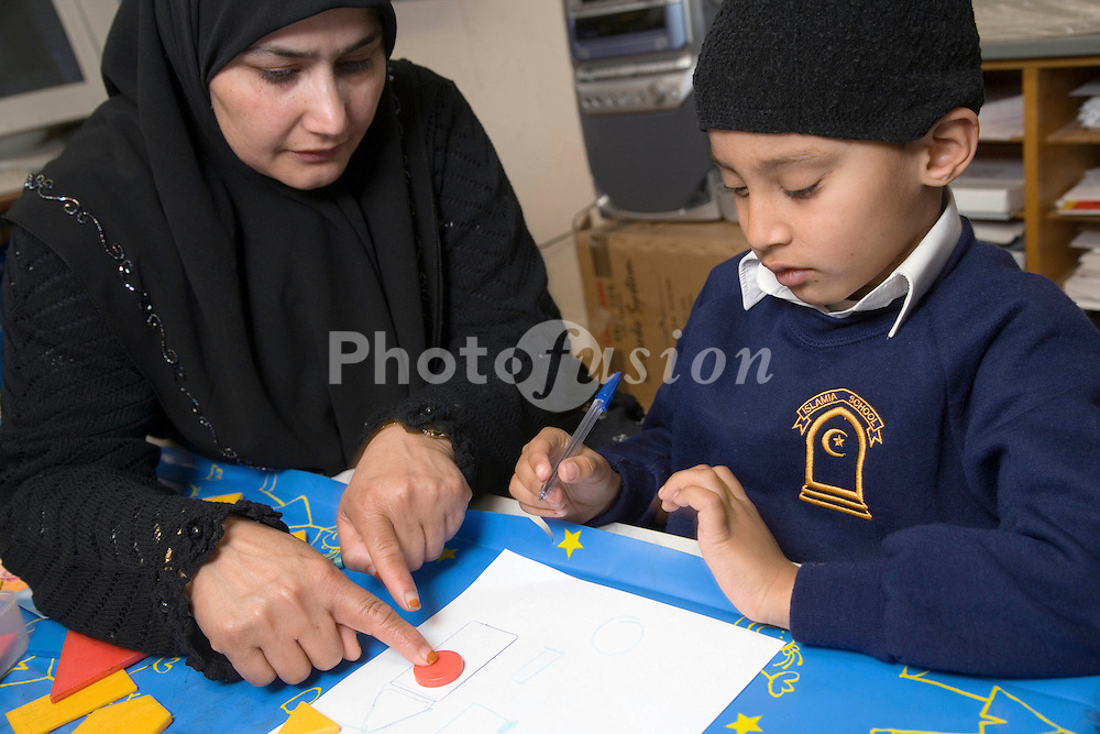 Teacher helping a pupil in a lesson at the Nottingham Islamia school,