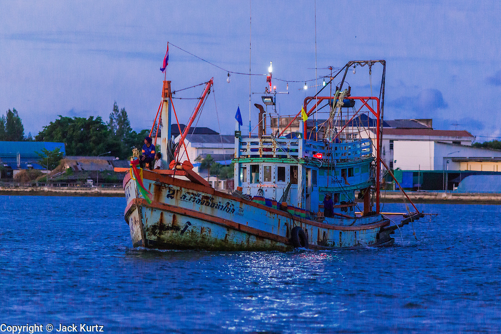 30 APRIL 2013 - MAHACHAI, SAMUT SAKHON, THAILAND:    A Thai fishing trawler returns to port in Mahachai after a fishing trip in the Gulf of Siam. The Thai fishing industry is heavily reliant on Burmese and Cambodian migrants. Burmese migrants crew many of the fishing boats that sail out of Samut Sakhon and staff many of the fish processing plants in Samut Sakhon, about 45 miles south of Bangkok. Migrants pay as much $700 (US) each to be smuggled from the Burmese border to Samut Sakhon for jobs that pay less than $5.00 (US) per day. There have also been reports that some Burmese workers are abused and held in slavery like conditions in the Thai fishing industry.        PHOTO BY JACK KURTZ