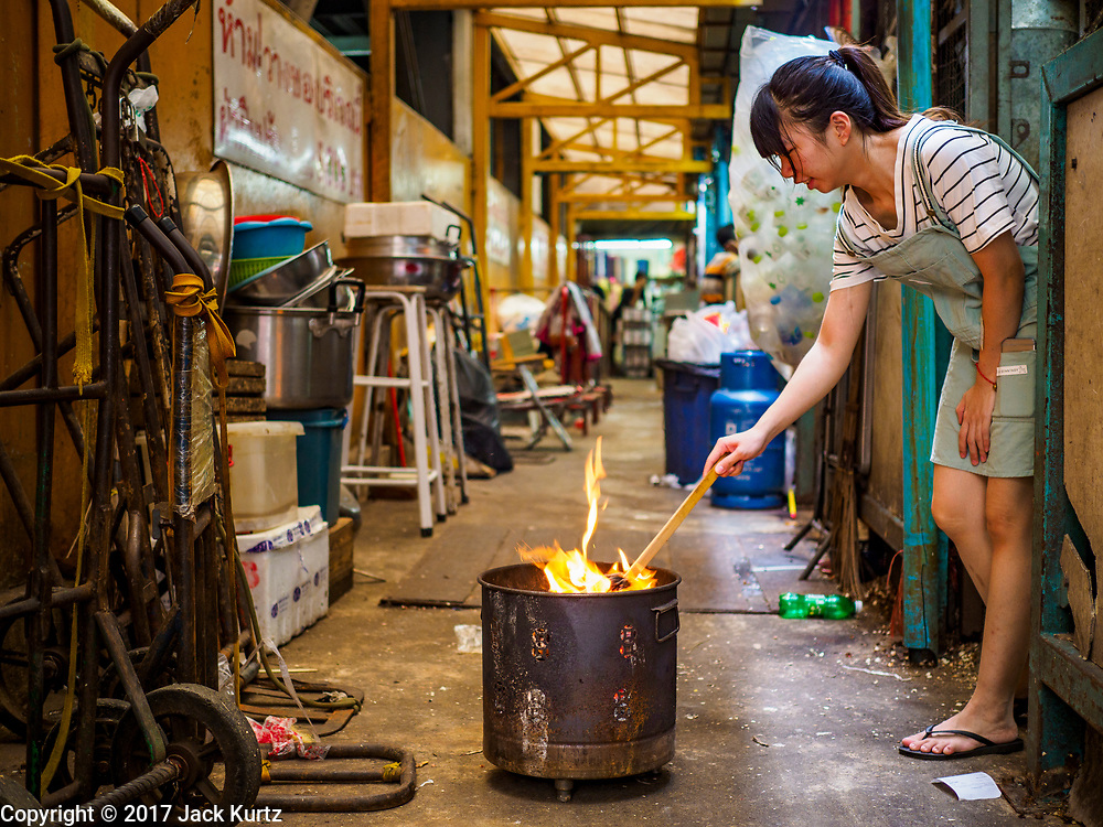 "22 AUGUST 2017 - BANGKOK, THAILAND: A woman burns ""Ghost Money"" in an alley in the Chinatown section of Bangkok on the first day of Hungry Ghost month. The seventh lunar month (August - September) is when many Chinese believe Hell's gate will open to allow spirits to roam freely in the human world. Many households and temples hold prayer ceremonies throughout the month-long Hungry Ghost Festival (Phor Thor) to appease the spirits. During the festival, believers will also worship the Tai Su Yeah (King of Hades) in the form of paper effigies which will be ""sent back"" to hell after the effigies are burnt.      PHOTO BY JACK KURTZ"