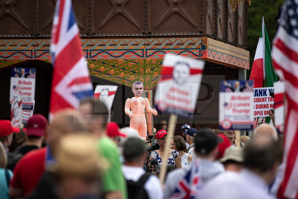 """© Licensed to London News Pictures. 14/07/2018. London, UK. An inflatable sex doll with the face of London Mayor Sadiq Khan is head aloft . Supporters of US President Donald Trump and EDL founder Tommy Robinson ( real name Stephen Yaxley-Lennon ) hold a """" Welcome Trump """" demonstration opposite the American Embassy . Trump is currently in Scotland and Robinson is in HMP Hull . Photo credit: Joel Goodman/LNP"""