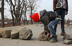 A young boy lays stones to block a road during a protest against unscheduled power cuts on the outskirts of Srinagar, summer capital of Indian-controlled Kashmir, Jan. 8, 2013. Locals said that only three hours of power supply was provided daily for the past several weeks, which led to the worsening of the living condition in the cold weather, January 8, 2013. Photo by Imago / i-Images...UK ONLY