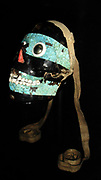 Turquoise mosaic mask of Tezcatlipoca, Mixtec-Aztec, AD 1400-1521. A human skull forms the base for this mask of Tezcatlipoca. 'Smoking Mirror', one of four powerful creator gods in the Aztec pantheon. The Aztec believed that the defeat of Quetzalcoatl by Tezcatlipoca marked the beginning of the current era of creation.  The emblem of Tezcatlipoca, an obsidian mirror, symbolises his control over the hidden forces of creation and destruction.  The mask is decorated with a mosaic of turquoise, lignite and shell; the eyes have been made from polished iron pyrites.  The skull was probably tied around the waist by the leather straps as indicated in the Codex image.