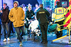 "© Licensed to London News Pictures . 22/12/2018 . Manchester , UK . A women requiring the assistance of firefighters , paramedics and police is carried on a trolley from the Hard Rock Cafe on Withy Grove . Revellers out in Manchester City Centre overnight during "" Mad Friday "" , named for historically being one of the busiest nights of the year for the emergency services in the UK . Photo credit : Joel Goodman/LNP"
