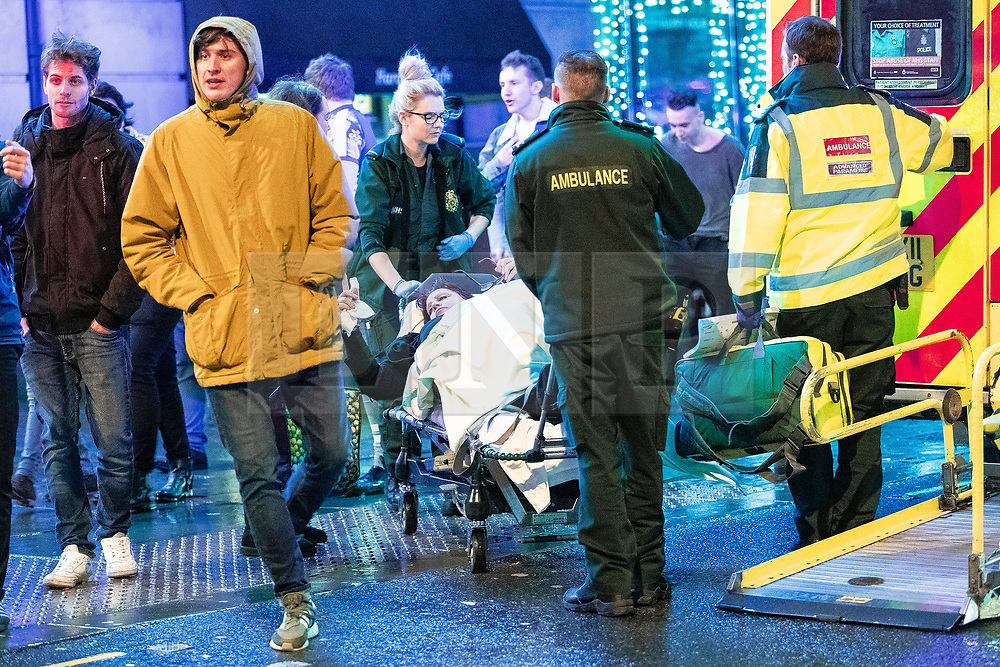 """© Licensed to London News Pictures . 22/12/2018 . Manchester , UK . A women requiring the assistance of firefighters , paramedics and police is carried on a trolley from the Hard Rock Cafe on Withy Grove . Revellers out in Manchester City Centre overnight during """" Mad Friday """" , named for historically being one of the busiest nights of the year for the emergency services in the UK . Photo credit : Joel Goodman/LNP"""