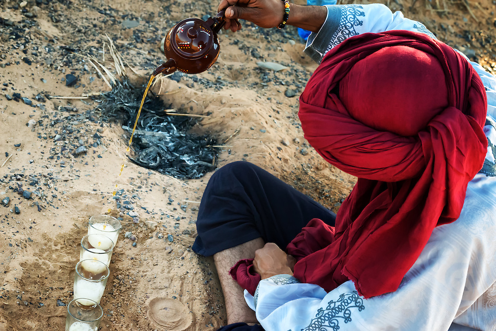 Moroccan man with red turban prepares traditional mint tea in the desert.