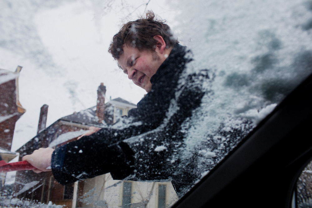 Andrew Spear, 23, scrapes ice from his windshield on a cold and snowy morning in Columbus, Ohio on Friday, February 25, 2011. SB5 would eliminate collective bargaining rights for state workers, which Governor John Kasich claims is a necessary reaction to the budget crisis.