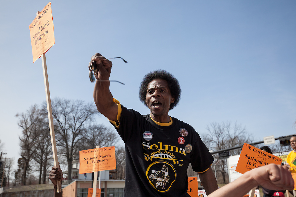 A protester speaks to the gathered crowd during a rally in front of the Ferguson police department.