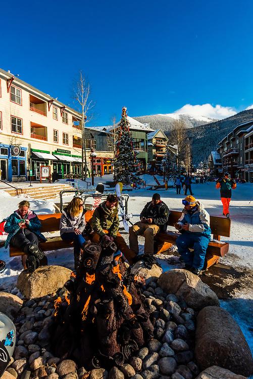 Skiers enjoy apres ski around an outdoor firepit, River Run Village, Keystone Resort, Colorado USA.