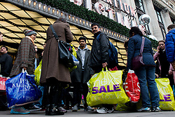 Boxing Day Sales. Shoppers with shopping bags stand outside Selfridges department store on Boxing Day. Shoppers flock to the traditional Boxing Day sales in London to search the best post-Christmas sales. Selfridges, London, United Kingdom. Thursday, 26th December 2013. Picture by Peter Kollanyi / i-Images