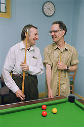 Two men with learning disabilities talking and laughing at pool table in community centre,