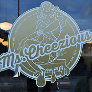 Pin-up inspired logo on the front door of the restaurant, along with their website and when Ms. Cheezious was first established (photo by Lia Latty).