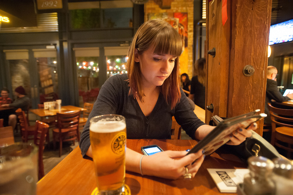 Young woman sitting at a bar looking at a menu in Salt Lake City, Utah