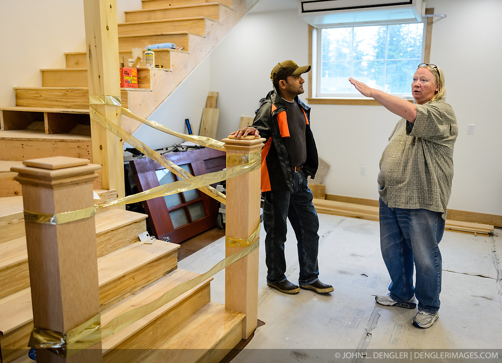 Joanne Waterman (right) explains to Nishan Weerasinghe of Haines the partially completed staircase in the restored fire hall tower located on the grounds of historic Fort William H. Seward, located in Haines, Alaska.<br /> <br /> The fire hall was restored over a two-year period by owners Waterman and Phyllis Sage who also own the fort&rsquo;s original guardhouse, now a bed and breakfast, located next door to the fire hall.<br /> <br /> After being absent from the historic Fort Seward skyline since approximately the 1930s, the 60-foot tower of the fort&rsquo;s fire hall has been restored to its original height. The building and tower, built around 1904 in Haines, Alaska, was shortened to approximately half its height in the 1930s for unknown reasons. The restoration included rebuilding a missing 35-foot section of the 60-foot tower whose purpose was to dry fire hoses. The tower restoration was completed by building its four sections on the ground and then hoisting those sections with a crane into place on top of each other.<br /> <br /> Through the years, the historic Fort Seward area, a former U.S. Army post, has been referred to as Fort William H. Seward, Chilkoot Barracks, and Port Chilkoot. The National Historic Landmarks listing record for the fort says that &quot;Fort Seward was the last of 11 military posts established in Alaska during the territory's gold rushes between 1897 and 1904. Founded for the purpose of preserving law and order among the gold seekers, the fort also provided a U.S. military presence in Alaska during boundary disputes with Canada. The only active military post in Alaska between 1925 and 1940, the fort was closed at the end of World War II.&rdquo; <br /> <br /> The bottom portion of the fire hall is being leased as commercial space. Due to fire code restrictions there is no public access to the upper portion of the tower.
