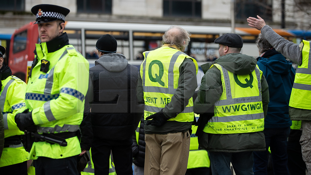 """© Licensed to London News Pictures . 09/02/2019. Manchester , UK . Two men wearing QAnon conspiracy theory yellow jackets at a """" Yellow Vest """" protest in Manchester City Centre , lead by James Goddard . The yellow vest concept has been adopted from French demonstrators by some British groups in support of Brexit , Donald Trump and former EDL leader Stephen Yaxley-Lennon - aka Tommy Robinson . A similar demonstration in the city in January was ridiculed after protesters were kettled by police in front of a branch of Greggs the Baker . Photo credit : Joel Goodman/LNP"""