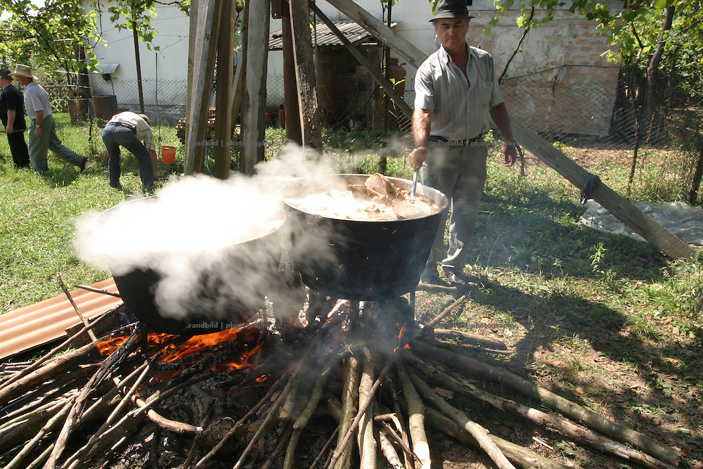 Georgien/Abchasien, Gudauta, 2006-08-26, Auf offenem Feuer wird das Fleisch einer Kuh gegart. Auf dem traditionellen Treffen des Hagba-Clans in Abchasien kommen 125 Familien zusammen. Vor dem Fest diskutieren die Männer die Probleme und sammeln Geld für notleidende Familienmitglieder. Abchasien erklärte sich 1992 unabhängig von Georgien. Nach einem einjährigen blutigen Krieg zwischen den Abchasen und Georgiern besteht seit 1994 ein brüchiger Waffenstillstand, der von einer UNO-Beobachtermission unter personeller Beteiligung Deutschlands überwacht wird. Trotzdem gibt es, vor allem im Kodorital immer wieder bewaffnete Auseinandersetzungen zwischen den Armee der Länder sowie irregulären Kämpfern.  (The meat of one cow boils on an open campfire. A meeting of the Hagba clan in Abkhazia. 125 families depends on that clan. At the traditional meeting every summer the men discuss the problems and collecting money for needy family members. After that the party begins. Abkhazia declared itself independent from Georgia in 1992. After a bloody civil war a UNO mission observing the ceasefire line between Georgia and Abkhazia since 1994. Nevertheless nearly every day armed incidents take place in the Kodori gorge between the both armys and unregular fighters )