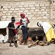 Yayi Bayam Diouf braise des moules, avec l'aide des enfants du quartier