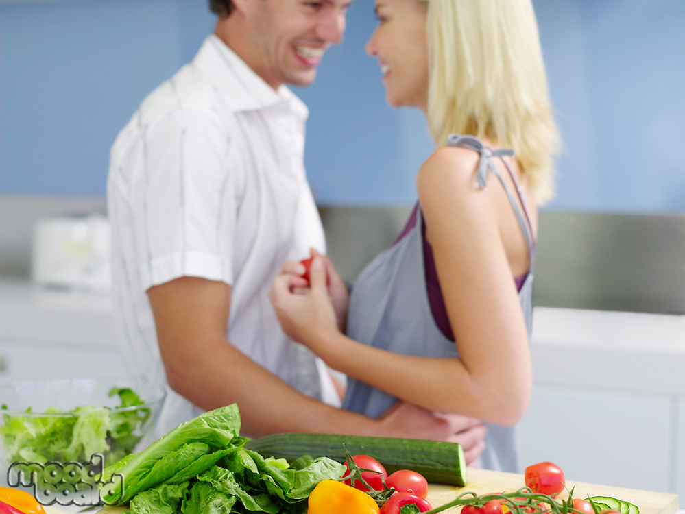 Young couple standing face to face Flirting in Kitchen near fresh produce side view