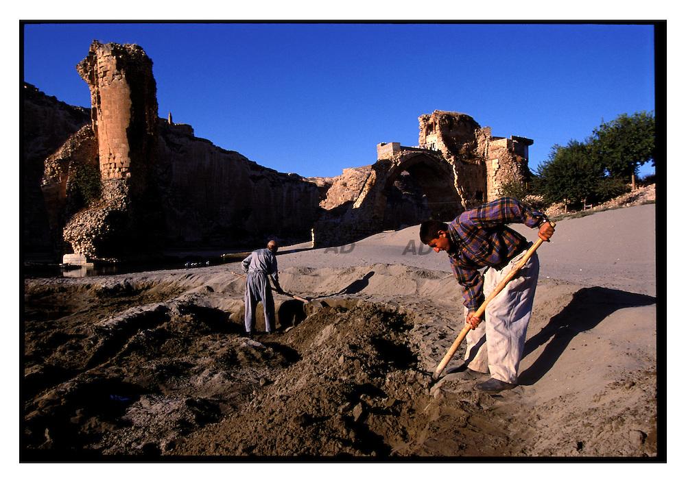 Memet e suo padre Osman raccolgono la sabbia per fare il cemento. Serve loro per rinforzare la stalla. Abitano a poche centinaia di metri dal fiume, vicino al ponte romano. Vorrebbero costruire una stalla nuova, ma non sanno ancora che fine faranno loro e la loro casa.