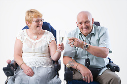 Disabled couple toasting one another with a glass of Champagne,
