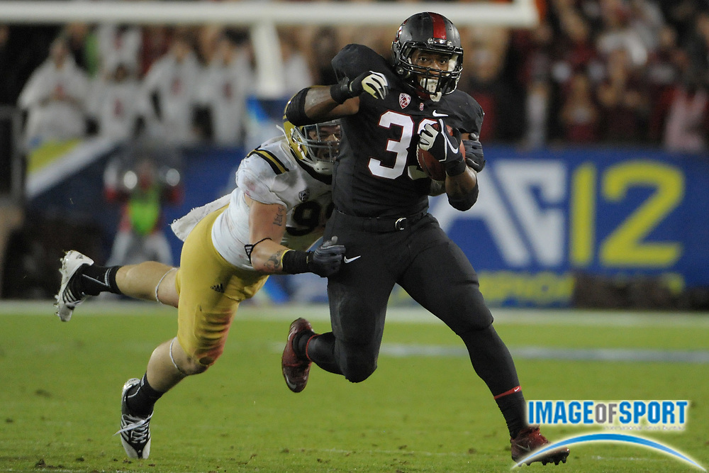November 30, 2012; Stanford, CA, USA; Stanford Cardinal running back Stepfan Taylor (33) runs the ball against UCLA Bruins defensive end Cassius Marsh (99) during the first quarter of the Pac-12 Championship game at Stanford Stadium.