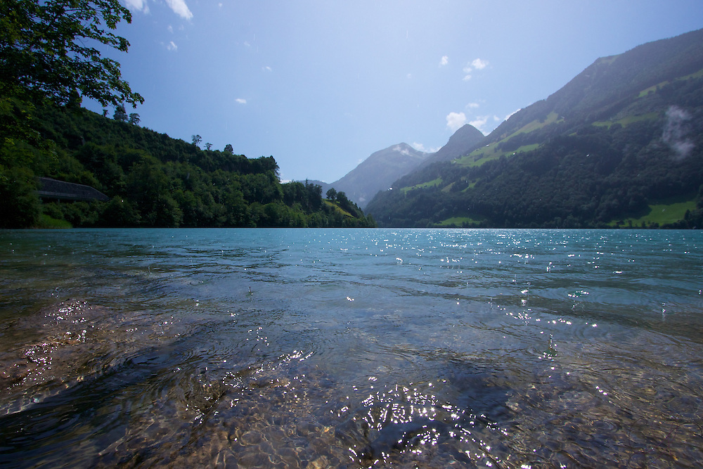 Lungersee on a summer day - an almost impossible azure blue alpine lake is the centerpiece of Lungern
