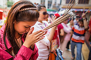 "10 FEBRUARY 2013 - BANGKOK, THAILAND:  A woman prays on Chinese New Year at a shrine on the grounds of the Thian Fah Hospital, a Chinese hospital in the Chinatown section of Bangkok. Bangkok has a large Chinese emigrant population, most of whom settled in Thailand in the 18th and 19th centuries. Chinese, or Lunar, New Year is celebrated with fireworks and parades in Chinese communities throughout Thailand. The coming year will be the ""Year of the Snake"" in the Chinese zodiac.   PHOTO BY JACK KURTZ"