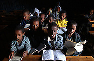 Dessie, Ethiopia: Third-grade students crowd into a stream of light coming from a window in the Showber Islamic School, which has no electricity, and is barely hanging on financially. The Wallo region is known as a place where Muslims and Christians have gotten along, intermarried and intermingled. In recent years, however, a kind of competition has developed between the two faiths. These children are learning to read the Koran in Arabic. (PHOTO: MIGUEL JUAREZ LUGO)