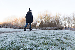 © Licensed to London News Pictures. 27/12/2016. Horsham, West Sussex, UK.  A woman walks on frost covered ground in Horsham, West Sussex. Parts of the south of England have woken to frost and freezing weather this morning.  Photo credit: Vickie Flores/LNP