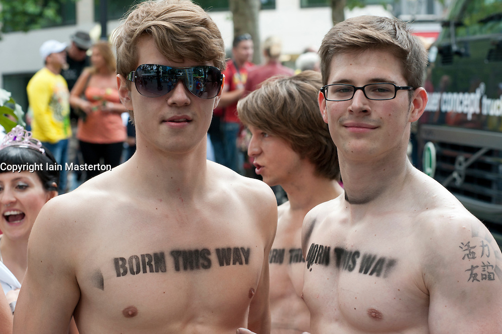 Men with gay pride message stenciled on their bare chests at the Christopher Street Day Parade in Berlin Germany 2011