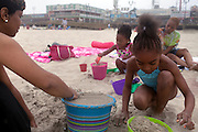 Seaside Heights, NJ - June 30, 2013 :  Joya Allen, left, with Annaela Scott, 8, with her sister Alyssa Scott, 3, and mother Sheryia Scott build sandcastles in front of the boardwalk at Seaside Heights, NJ on June 30, 2013. People are returning to the beaches for the summer after recovery efforts post Superstorm Sandy.