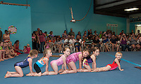 """Gymmy's"" Rory Rousseau, Catherine Fay, Mary Louise Banker, Gracie Stephen, Sasha Kiel and Lyla McSheffrey do the ""caterpillar"" during their floor time at Lakes Region Gymnastics Friday evening.  (Karen Bobotas/for the Laconia Daily Sun)"