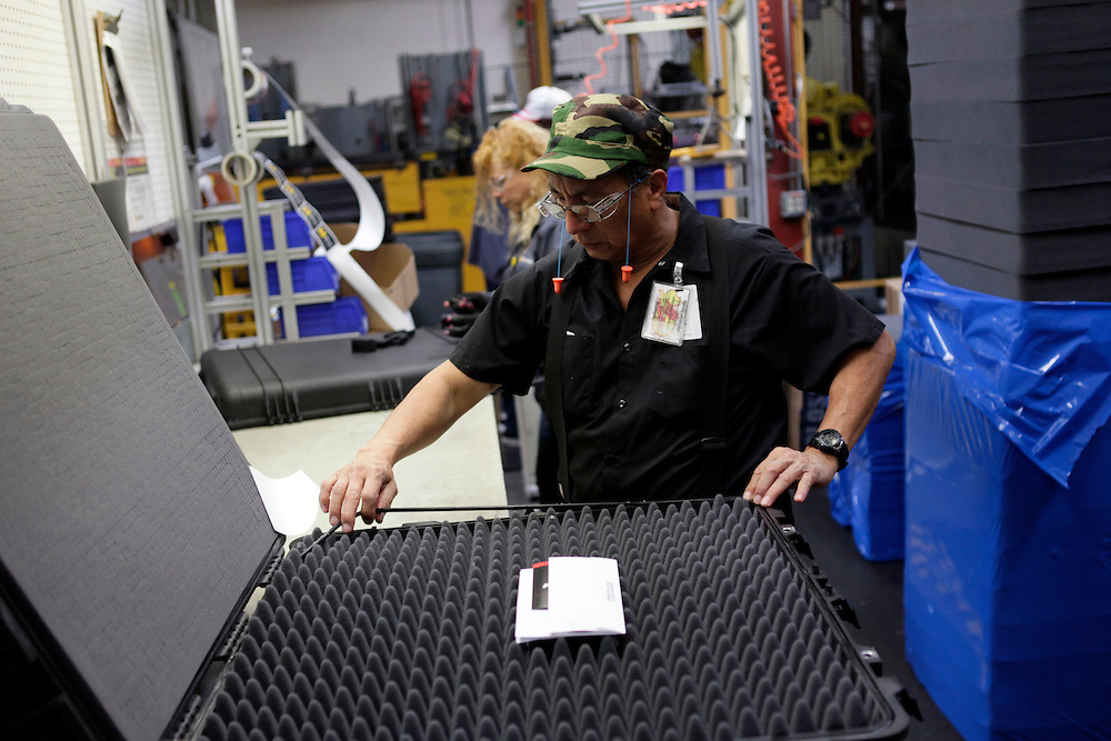 A worker installs an o-ring and foam in an injection-molded plastic hardshell case at the Pelican Products Inc. production facility in Torrance, California, U.S., on Thursday, March 8, 2012. © 2012 Patrick T. Fallon