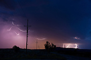 Cloud-to-cloud lightning in sky over power lines with distant cloud-to-ground lightning from separate storm cell, © 2014 David A. Ponton
