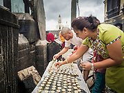 31 JULY 2015 - KATHMANDU, NEPAL: People light butter lamps at  Swayambhunath Stupa, a large Buddhist stupa in Kathmandu. Parts of the stupa were badly damaged in the Nepal earthquake of 2015 but it is still open for religious devotees and tourists. Construction of the stupa started in the 1600s.    PHOTO BY JACK KURTZ