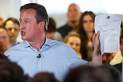© Licensed to London News Pictures. 05/05/2015. LONDON, UK. Conservatives leader and Prime Minister David Cameron showing the letter left in the treasury by Labour government in 2010 whilst speaking to staff at Utility Warehouse in Hendon, northwest London on Tuesday, 5 May 2015. Photo credit : Tolga Akmen/LNP