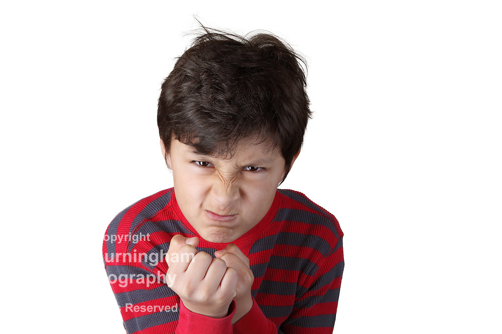 Mad angry boy with clenched fists on white isolated background