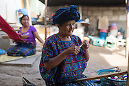 "Margarita ""Abuelita"" Perez, creates a bracelet which will be sold to tourists in Panajachel. The women of the Perez family work together to create clothing, jewelry and other textiles to support themselves."