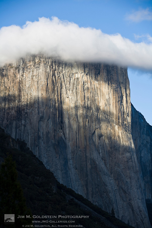 A cloud forms atop El Capitan shrouding the top of the cliff-face - Yosemite National Park, California
