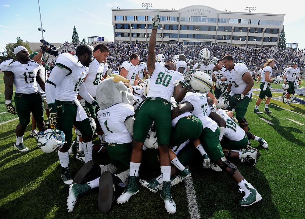 South Florida's Mike McFarland celebrates along with his team on the top of the pile after South Florida defeated Nevada 32-31 Saturday, Sept. 8, 2012 in Reno.