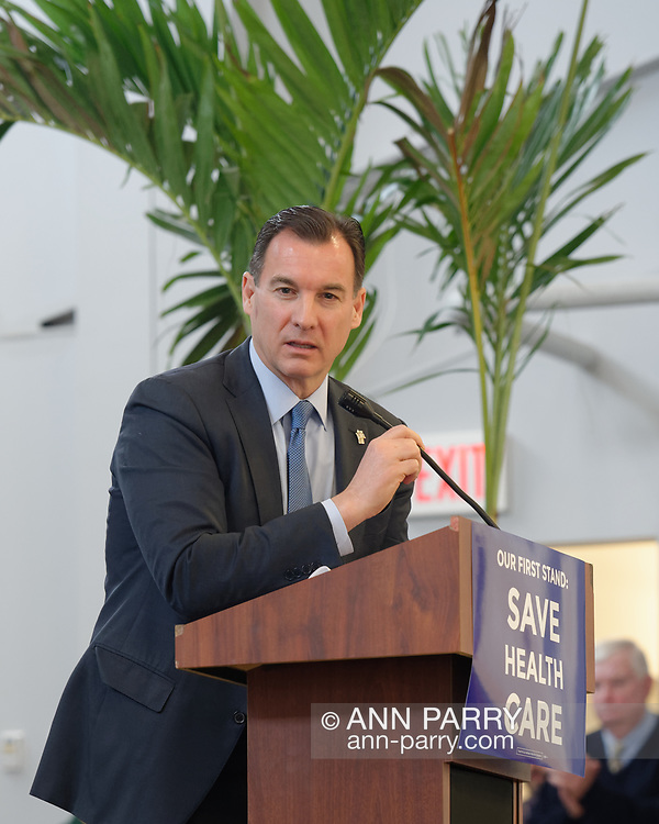 """Westbury, New York, USA. January 15, 2017. Representative THOMAS SUOZZI (Democrat - 3rd Congressional District NY), standing on stage speaking at podium, is one of the hosts at the """"Our First Stand"""" Rally against Republicans repealing the Affordable Care Act, ACA, taking millions of people off health insurance, making massive cuts to Medicaid, and defunding Palnned Parenthood. Rep. K. Rice (Democrat - 4th Congressional District) was also a host."""