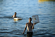 Palestinian fishermen try to catch small fish inside Gaza harbor August 05, 2007 in Gaza. Under the Palestinian Authority, fishermen were able to get permission from the Israeli Navy, which maintains a blockade just off the coast of Gaza, to fish several miles from shore. Since the takeover of Gaza by Hamas in June, fisherman have had a much tougher time getting the permission, and have been forced to  fish close to shore or not leaving port at all, creating a further economic crisis in the strip. .