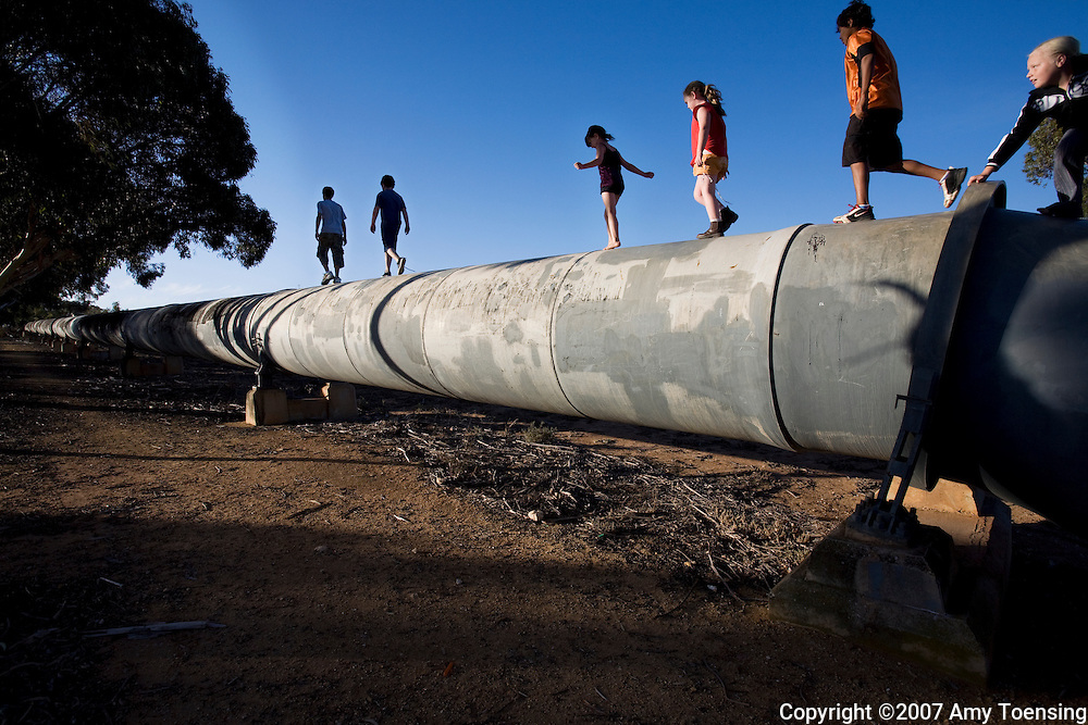 MANNUM, SA, AUSTRALIA - FEBRUARY 29: Kids play on the Mannum-Adelaide Pipeline that runs through a neighborhood February 29, 2008 in Mannum, South Australia, Australia. The Mannum-Adelaide Pipeline was the first major pipeline built from the River Murray to serve the water needs of Adelaide. Adelaide depends on water from the Murray-Darling Basin irrigation system and while the city uses far less water than irrigating farmers, the city has been actively promoting and implementing schemes that save water. The Murray-Darling Basin has been plagued with severe drought since the late 1990s and many growers and policy makers are being forced to find more efficient irrigation systems. (Photo by Amy Toensing/ Reportage by Getty Images). _________________________________<br />
