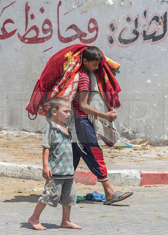 "© Licensed to London News Pictures. 15/07/2014. Gaza.  Two young boys carry a rug as his family prepare to leave the school they have been seeking refuge in as the conflict entered it's eighth day.   News of a potential ceasefire reached Gazan families who have been living in  the Al Fakoura school on the outskirts of the Bet Lahia district of Gaza.  It has been home to over 600 families during the current Isreal/Gaza conflict known as Operation Protective Edge.<br /> <br /> The ceasefire calls came ahead of an urgent meeting of Arab League foreign ministers in Cairo. There are still no clear indications that a ceasefire has been agreed and although Israel have accepted the conditions,  however, the armed wing of Hamas, which controls Gaza, rejected the initiative as a ""surrender"".  Photo credit : Alison Baskerville/LNP"