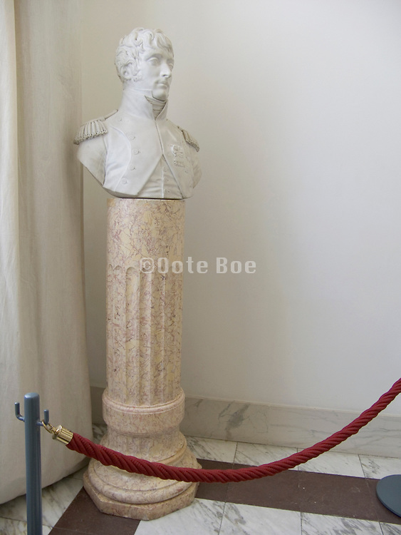a classic French statue on pedestal in the corner of a room
