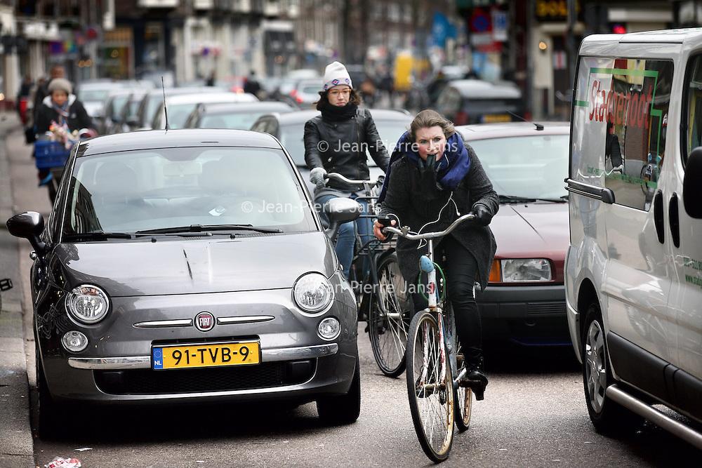 Nederland, Amsterdam , 20 maart 2013..Fietsers in de van Woustraat tussen het autorijverkeer..de fiets in Amsterdam dreigt aan zijn eigen succes ten onder  te gaan: er rijden inmiddels zóveel fietsers in de stad dat a) veel fietspaden te smal blijken en b) met name rond stations en in winkelgebieden er een groot tekort is aan fietsparkeerplekken.. Drukke fietsroutes, bijvoorbeeld de Weteringschans bij het Leidseplein (waar tussen vier en zes uur dagelijks gemiddeld 3500 fietsers passeren)..En verder alles waaruit blijkt dat fietsers in de knel zitten tussen alle andere soorten verkeer (auto, tram etcetera)..The bike in Amsterdam is likely to perish through its own success: There are too many cyclists, too little parking, too little space and too much traffic.