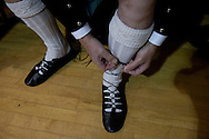 A guest tying the laces on his dancing shoes at a St. Andrew's dinner dance held by the Sandbach and District Caledonian Society at Sandbach Town Hall, Cheshire, England on St. Andrew's Day. Around 40 people from the Society attended the meal and dance which included a programme of Scottish country dancing. St. Andrew was the patron saint of Scotland and the day was celebrated by Scots worldwide on the 30th November.